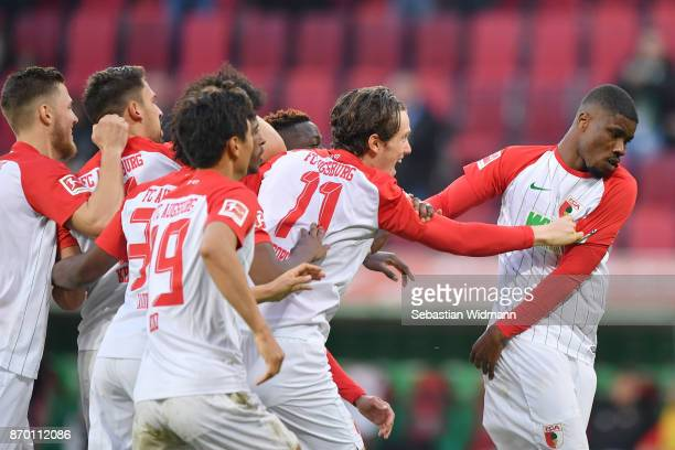 Teammates of Kevin Danso of Augsburg congratulate him on scoring his teams first goal during the Bundesliga match between FC Augsburg and Bayer 04...