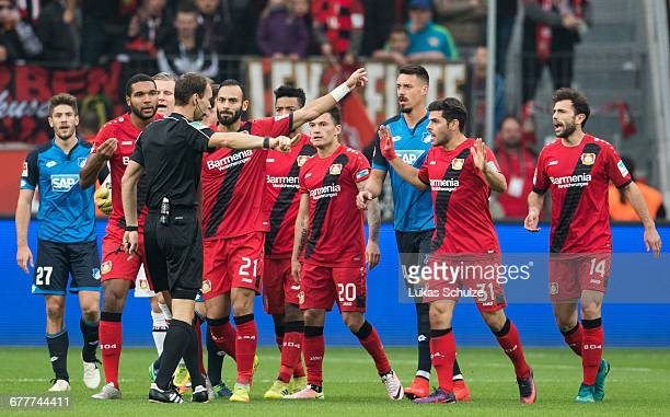 Teammates of Leverkusen and Kevin Volland of Leverkusen talk to referee Bastian Dankert who issues the red card to Volland during the Bundesliga...