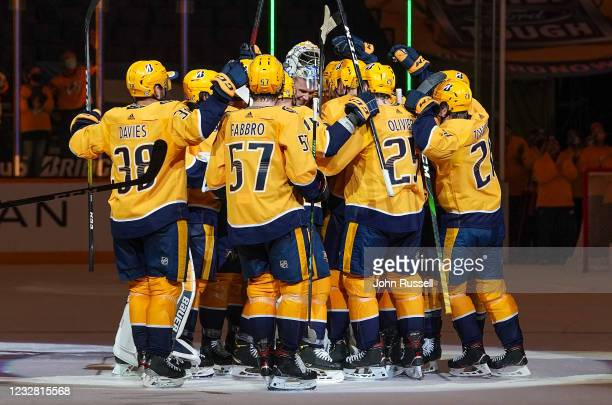 Teammates of Pekka Rinne of the Nashville Predators gather around him to celebrate his long career and a 5-0 win against the Carolina Hurricanes at...