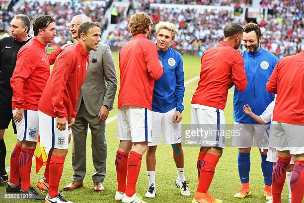 Teammates of Rest of the World and England greet one another during Soccer Aid at Old Trafford on June 5, 2016 in Manchester, England.