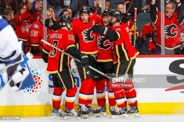 Teammates of the Calgary Flames celebrate in an NHL game on February 1 2018 at the Scotiabank Saddledome in Calgary Alberta Canada