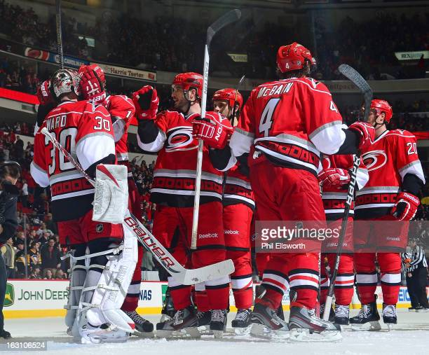 Teammates of the Carolina Hurricanes celebrate their victory over the Pittsburgh Penguins during an NHL game on February 28 2013 at PNC Arena in...