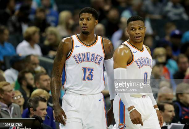Teammates Paul George and Russell Westbrook of the Oklahoma City Thunder watch on against the Charlotte Hornets during their game at Spectrum Center...