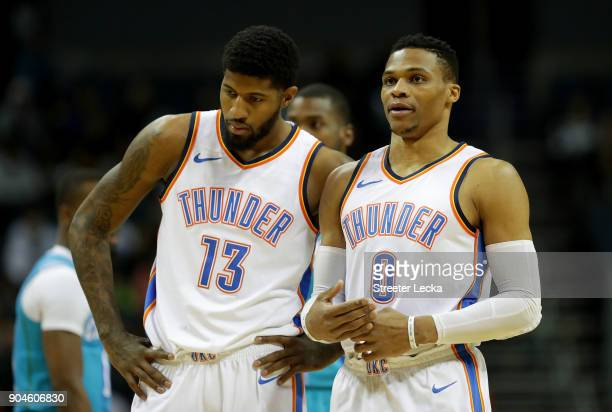 Teammates Paul George and Russell Westbrook of the Oklahoma City Thunder talk during their game against the Charlotte Hornets at Spectrum Center on...