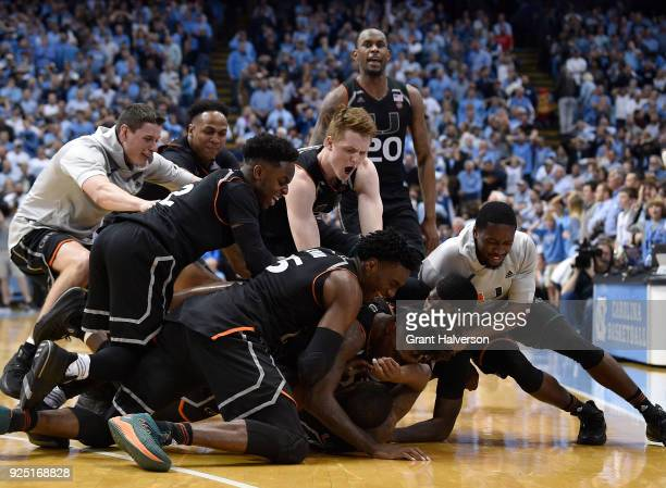 Teammates pile on Ja'Quan Newton of the Miami Hurricanes as they celebrate after his gamewining basket against the North Carolina Tar Heels during...