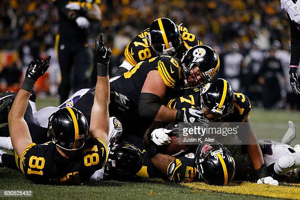 Teammates pile on Le'Veon Bell of the Pittsburgh Steelers after he scores a 7 yard touchdown in the fourth quarter during the game against the...