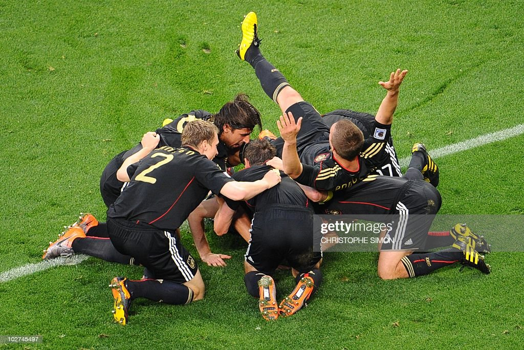 Teammates pile on top of Germany's defender Arne Friedrich after he scores the team's third goal during the 2010 World Cup quarter-final football match between Argentina and Germany on July 3, 2010 at Green Point stadium in Cape Town. NO