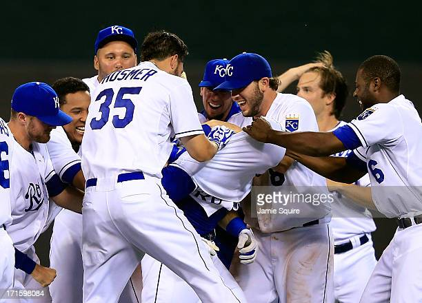 Teammates pull the shirt over the head of Alex Gordon of the Kansas City Royals after Gordon delivered the gamewinning hit in the 10th inning of the...