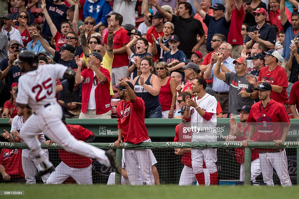 Teammates react as Jackie Bradley Jr. #25 of the Boston Red Sox rounds first base after hitting an RBI double during the eighth inning of game against the Tampa Bay Rays on August 31, 2016 at Fenway Park in Boston, Massachusetts.