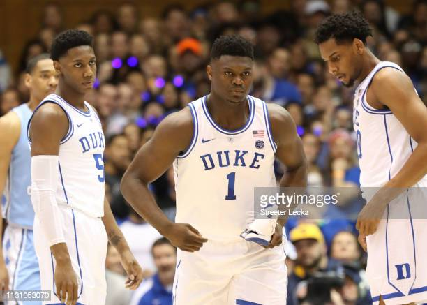 Teammates RJ Barrett and Marques Bolden of the Duke Blue Devils watch as Zion Williamson of the Duke Blue Devils reacts after falling as his shoe...