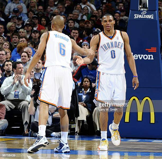 Teammates Russell Westbrook and Eric Maynor of the Oklahoma City Thunder give each other five during a break in the game against the San Antonio...