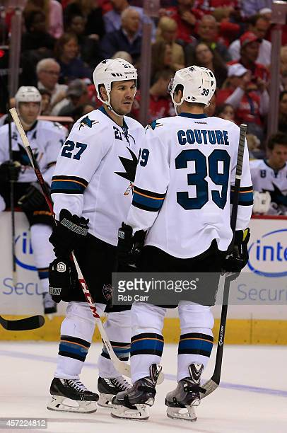 Teammates Scott Hannan and Logan Couture of the San Jose Sharks talk on the ice during the third perioid against the Washington Capitals at Verizon...