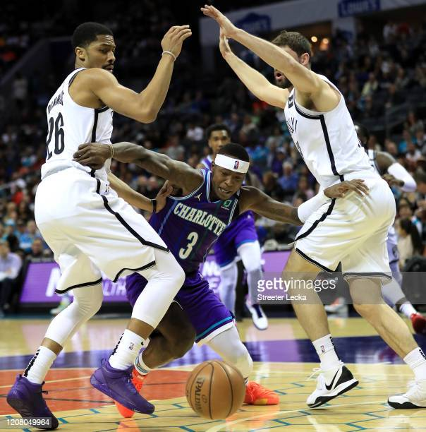 Teammates Spencer Dinwiddie and Joe Harris of the Brooklyn Nets try to stop Terry Rozier of the Charlotte Hornets during their game at Spectrum...
