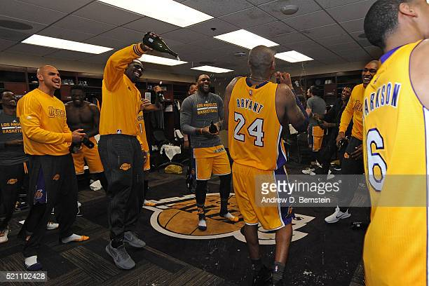 Teammates spray champagne on Kobe Bryant of the Los Angeles Lakers as he comes back to the locker room after the game against the Utah Jazz on April...