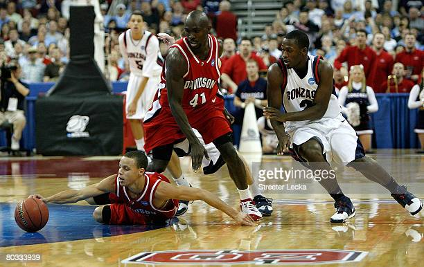 Teammates Stephen Curry and Andrew Lovedale of the Davidson Wildcats dive for a loose ball as Jeremy Pargo of the Gonzaga Bulldogs watches on during...