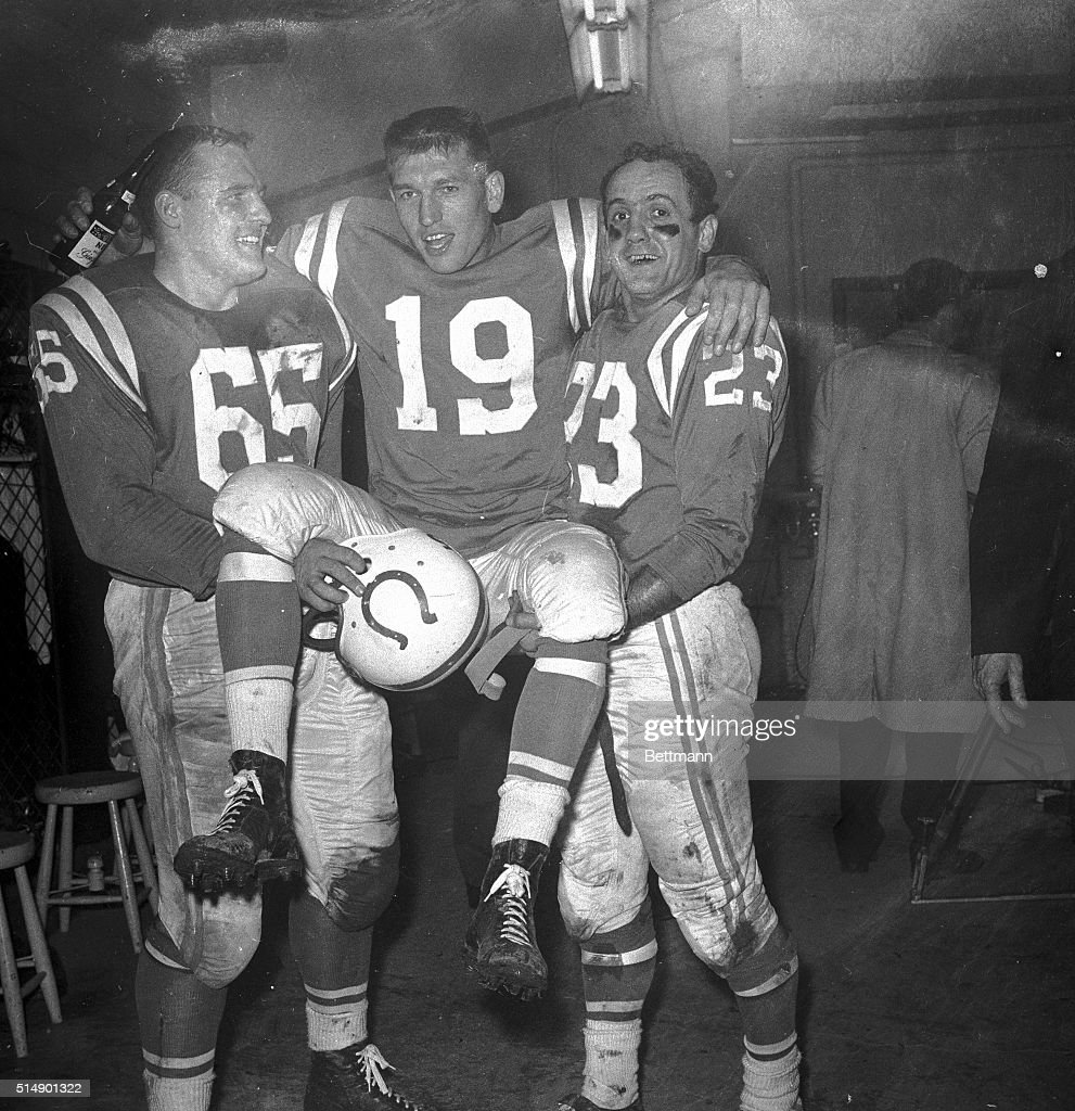 Teammates Steve Myhra (left) and Carl Tasoff (right) carry Baltimore quarterback Johnny Unitas into the dressing room after the Colts defeated the Giants 31-16 in the championship game.