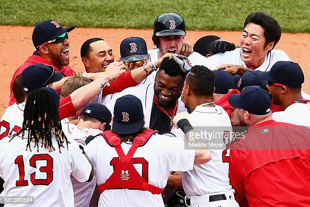 Teammates swarm David Ortiz of the Boston Red Sox center after hitting his game winning double during the eleventh inning against the Houston Astros...