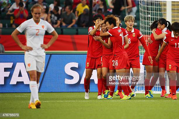 Teammates swarm Wang Lisi of China PR after she scored the game winning goal against the Netherlands during the FIFA Women's World Cup Canada 2015...