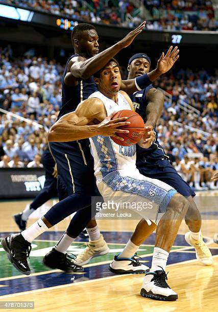 Teammates Talib Zanna and Jamel Artis of the Pittsburgh Panthers try to stop James Michael McAdoo of the North Carolina Tar Heels during the...