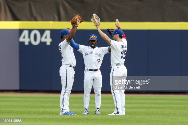 Teammates Teoscar Hernandez, Jonathan Davis, and Randal Grichuk, all of the Toronto Blue Jays, celebrate after defeating the Texas Rangers 10-0 in...