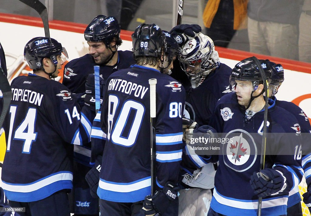 Teammates Tim Stapleton #14, Zach Bogosian #4, Nik Antropov #80 and Andrew Ladd #16 congratulate Ondrej Pavelec #31of the Winnipeg Jets after defeating the Montreal Canadiens in NHL action at the MTS Centre on December 22, 2011 in Winnipeg, Manitoba, Canada.