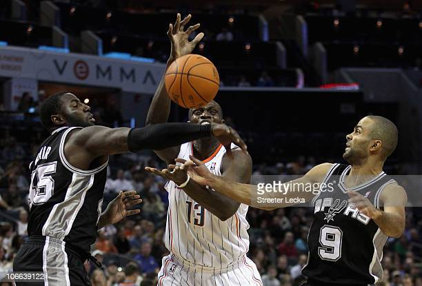 Teammates Tony Parker and DeJuan Blair of the San Antonio Spurs battle for a loose ball with Nazr Mohammed of the Charlotte Bobcats during their game...