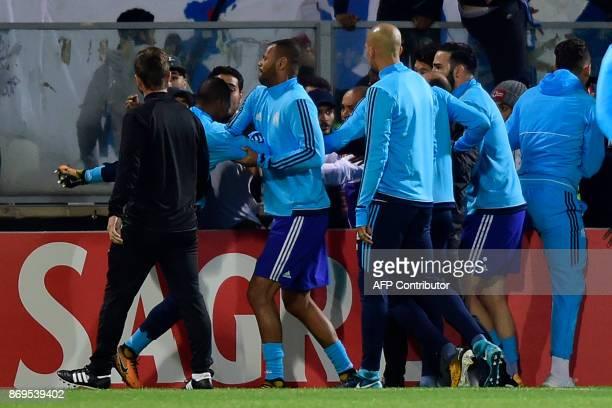 TOPSHOT Teammates try to calm down Marseille's defender Patrice Evra as he tries to kick a supporter before the start of the UEFA Europa League group...