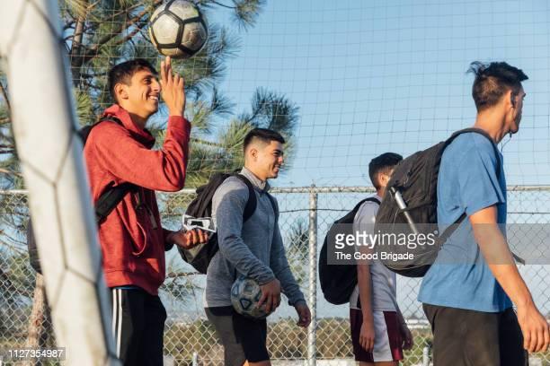 Teammates walking off soccer field after match