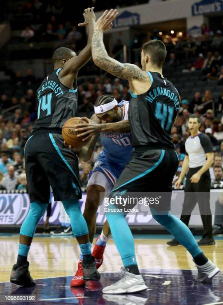 Teammates Willy Hernangomez and Michael KiddGilchrist of the Charlotte Hornets try to stop Willie CauleyStein of the Sacramento Kings during their...
