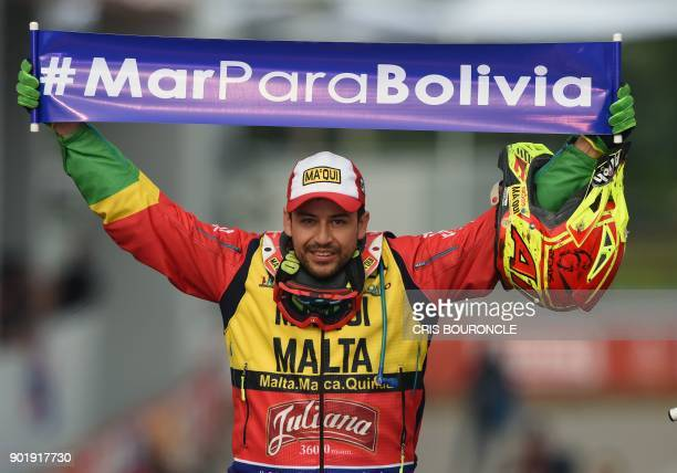 MEC Team's Bolivian quad rider Hernan Paredes on his Honda displays a banner reading 'Sea for Bolivia' on the podium during the start of the 2018...