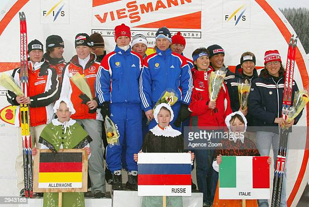Teams celebrate on the podium. Germany second place, Russia first place and Italy third Place in the Women's 4x5 km relay during the FIS World Cup...