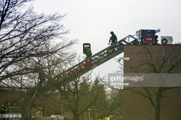 Teams descend from the roof of a King Soopers grocery store after a shooting on March 22, 2021 in Boulder, Colorado. Dozens of police responded to...