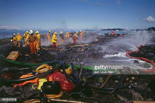 Teams of firefighters cleaning the Alaskan coast following the Exxon Valdez oil spill