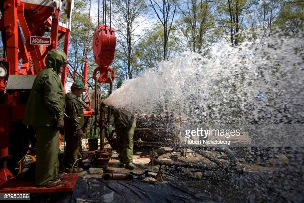 Teams of men from Minard Run Oil Company flush out water during a fracing operation at a 2100 foot natural gas well in Pleasant Valley Pennsylvania...