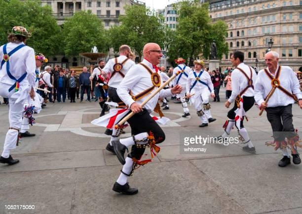 teams of morris dancers in trafalgar square, london - morris dancing stock photos and pictures