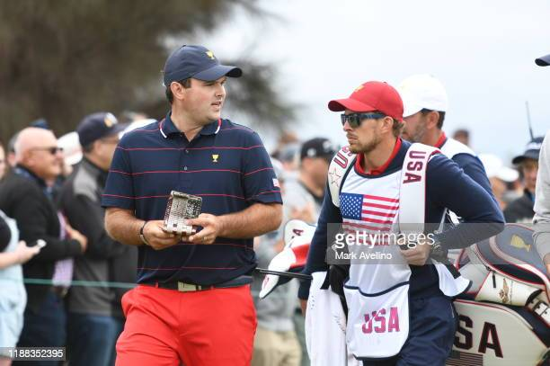 Team's Patrick Reed walks with his caddie Kessler Karain during the third round of four-ball matches at the Presidents Cup at The Royal Melbourne...