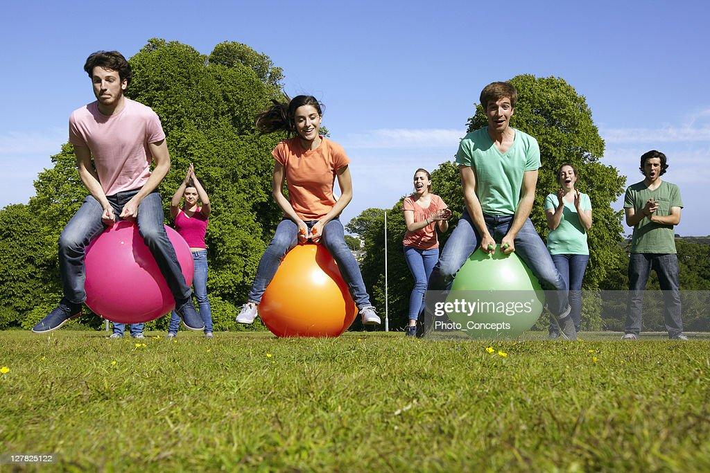 Teams racing on exercises balls : Stock Photo