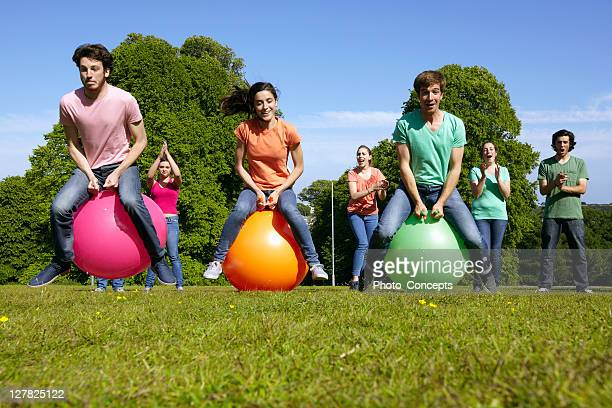teams racing on exercises balls - bouncing ball stock photos and pictures