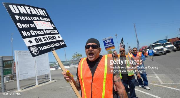 Teamster Hawk de Leon shouts 'What do we want Justice When do we want it Now' as he joins a protest at the Evergreen Terminal in the Port of Los...
