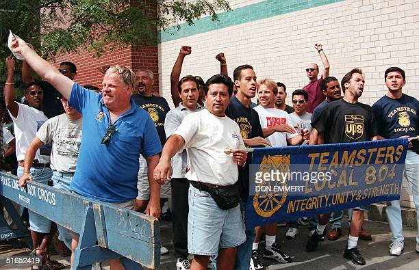 Teamsters at a UPS station in New York wave and cheer as supportive passing motorists honk their horns 19 August. The Teamsters union announced 18...