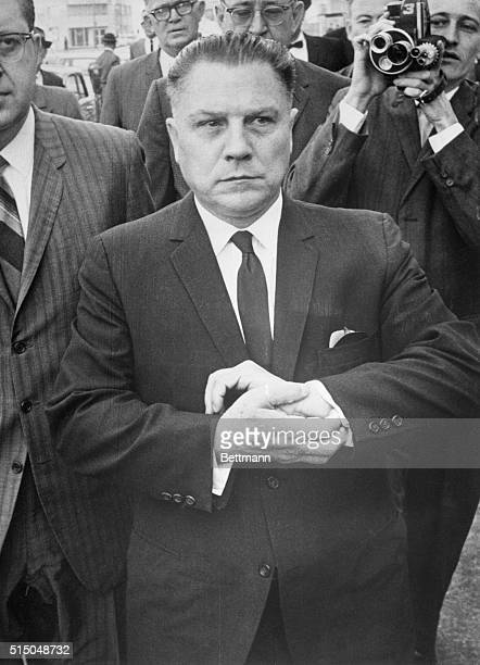 Teamsters boss Jimmy Hoffa, looking almost as if he had handcuffs on, leaves the Federal Courthouse here early 3/12 morning after Federal Judge Frank...
