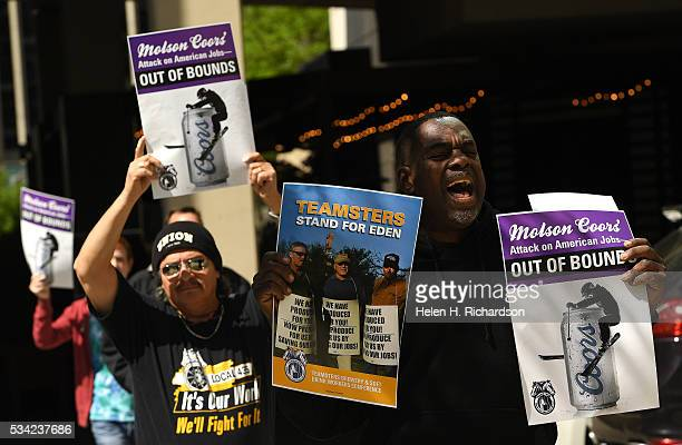 Teamsters Marc Dennis right and Jesse Medina in back join others as they hold signs to protest Molson Coors' annual shareholder meeting outside at...