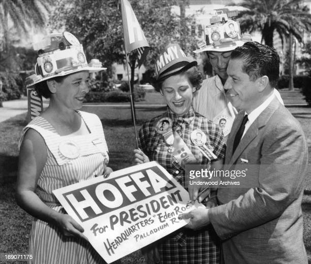 Teamsters union vice president JImmy Hoffa autographs a placard for him for a group of women campaigning for his run for president of the Teamsters,...