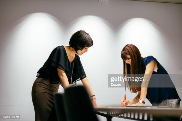 Teamwork and brainstorming with two Japanese businesswomen, working hard in order to achieve success