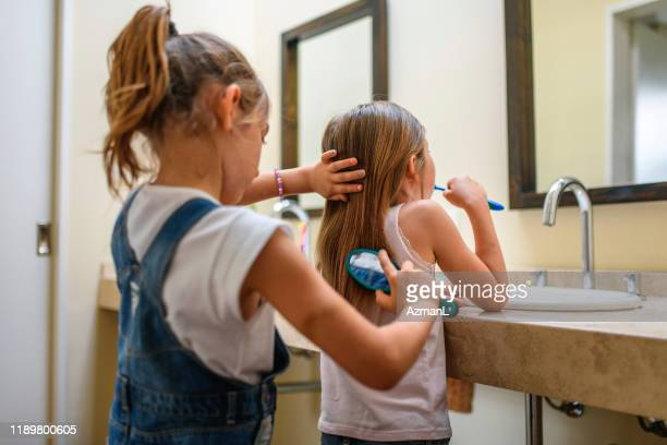 teamwork as young sisters brush teeth and hair - 6 7 anni foto e immagini stock