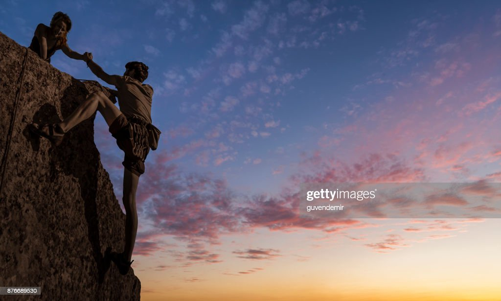 Teamwork couple climbing helping hand : Stock Photo