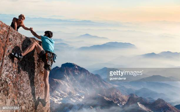 teamwork couple helping hand trust in inspiring mountains - climbing stock pictures, royalty-free photos & images
