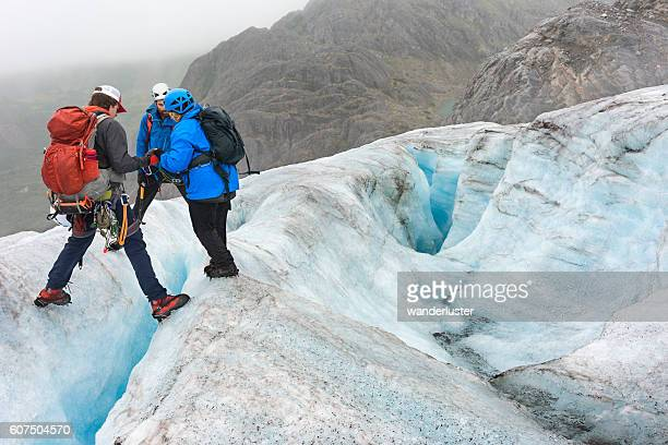 teamwork crossing crevasses - crevasse stock photos and pictures