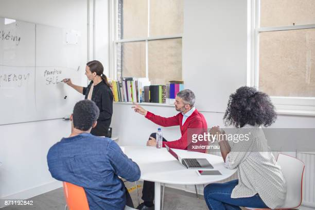 teamwork discussing about the new project using whiteboard - vanguardians stock pictures, royalty-free photos & images
