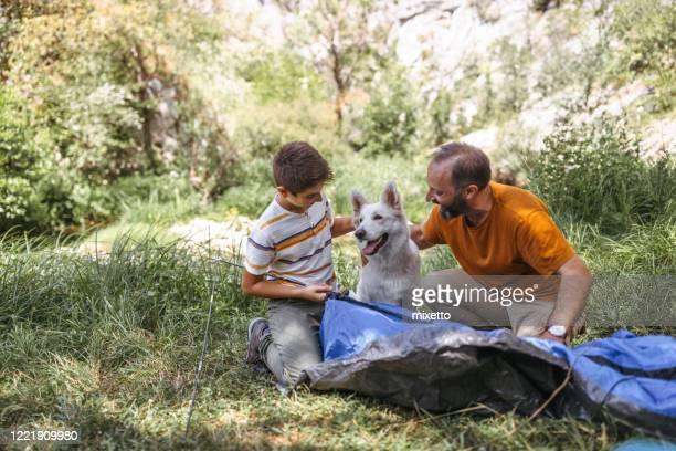 trabajo en equipo para la construcción de tiendas de campaña en el bosque - eden pastora fotografías e imágenes de stock